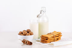 Fresh healthy milk, cookies with raisins, walnuts, cinnamon sticks on white background. selective focus. Stock Image