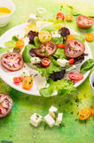 Fresh healthy mix salad with tomatoes, wild herbs, feta cheese on green background Royalty Free Stock Photography