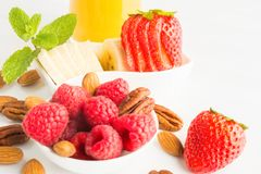 Fresh healthy morning or lunch bowl with nuts, strawberries, raspberries and juice. On white background royalty free stock images