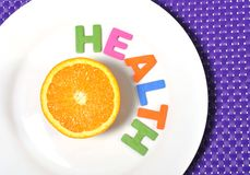Fresh healthy Orange Fruit and health word on plate Stock Photography