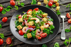Fresh Healthy Prawns salad with tomatoes, red onion on black plate. concept healthy food Stock Photos