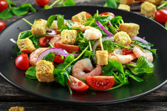 Fresh Healthy Prawns salad with tomatoes, red onion on black plate. concept healthy food Stock Image