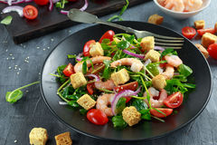 Fresh Healthy Prawns salad with tomatoes, red onion on black plate. concept healthy food Stock Images