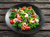 Fresh Healthy Prawns salad with tomatoes, red onion on black plate. concept healthy food Royalty Free Stock Photography