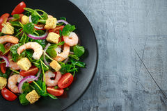 Fresh Healthy Prawns salad with tomatoes, red onion on black plate. concept healthy food Stock Photography