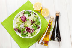 Fresh healthy salad and condiments over white wooden table Stock Images
