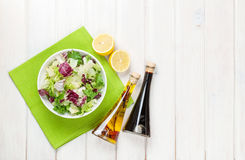 Fresh healthy salad and condiments over white wooden table Royalty Free Stock Images