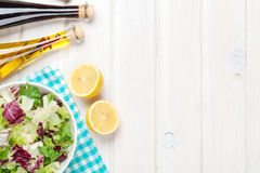 Fresh healthy salad and condiments over white wooden table Royalty Free Stock Photo