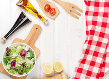 Fresh healthy salad and condiments over white wooden table Stock Image