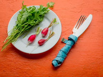 Fresh healthy salad and cutlery with measuring tape on orange table. Healthy food top view. Stock Image