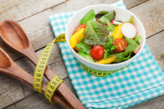 Fresh healthy salad and kitchen utensil Stock Photography