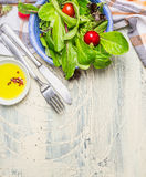 Fresh healthy salad with lettuce , cherry tomatoes and radish on light rustic background with cutlery and olive oil, top view, pla Royalty Free Stock Image
