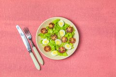 Fresh healthy salad on living coral table surface. Fresh healthy salad with lettuce, quail eggs, cherry tomatoes and sesame in plate. Top view, copy space stock image