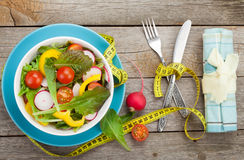 Fresh healthy salad and measuring tape. Healthy food Royalty Free Stock Photo