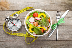 Fresh healthy salad and measuring tape on wooden table Royalty Free Stock Photography