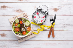 Fresh healthy salad and measuring tape on wooden table Royalty Free Stock Photos