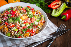 Fresh healthy salad with quinoa, colorful tomatoes, sweet pepper, cucumber and parsley on wooden background close up. Royalty Free Stock Photos