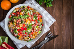 Fresh healthy salad with quinoa, colorful tomatoes, sweet pepper, cucumber and parsley on wooden background top view. Royalty Free Stock Photos