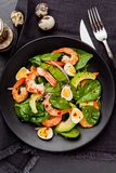 Fresh, healthy salad with shrimps, spinach and avocado on a blac Stock Photos