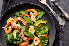 Fresh, healthy salad with shrimps, spinach and avocado on a blac Royalty Free Stock Photography