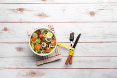 Fresh healthy salad, silverware and measure tape Royalty Free Stock Image