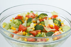 Fresh and healthy salad with tomatoes, broccoli, iceberg lettuce and sweet maize corn. Raw vegetables in a glass bowl. Selective focus, shallow depth of field Royalty Free Stock Images