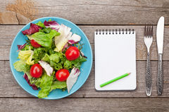 Fresh healthy salad with tomatoes and kitchen utensils Royalty Free Stock Photo