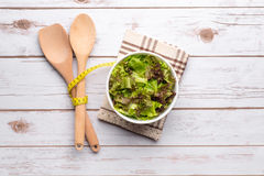 Fresh healthy salad, utensils and tape measure Royalty Free Stock Images
