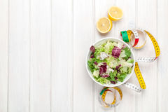Fresh healthy salad, utensils and tape measure over white wooden Royalty Free Stock Photography