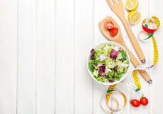 Fresh healthy salad, utensils and tape measure over white wooden Stock Photos
