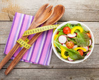 Fresh healthy salad on wooden table and kitchen utensil Royalty Free Stock Images