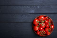 Fresh, healthy tomato vegetables in a bowl on a wooden table background. Copy space. Top view of wicked bowl full of beautiful, red, ripe, tomatoes on a dark Stock Images