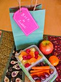 """Back to school """"green bag lunch"""" concept. Fresh, healthy, vegan food to pack for kids: mixed fruit salad and carrots in an open plastic container, apple and Royalty Free Stock Image"""