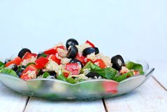 Fresh healthy vegan salad with quinoa, corn salad, black olives, red pepper and olive oil in glass bowl cloth on white wooden back Royalty Free Stock Photography