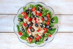 Fresh healthy vegan salad with quinoa, corn salad, black olives, red pepper and olive oil in glass bowl cloth on white wooden back Stock Photo