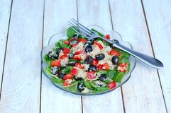 Fresh healthy vegan salad with quinoa, corn salad, black olives, red pepper and olive oil in glass bowl cloth on white wooden back Stock Photography