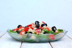 Fresh healthy vegan salad with quinoa, corn salad, black olives, red pepper and olive oil in glass bowl cloth on white wooden back Stock Image