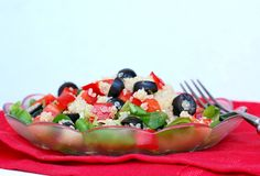 Fresh healthy vegan salad with quinoa, corn salad, black olives, red pepper and olive oil in glass bowl on red cloth on white wood Stock Image