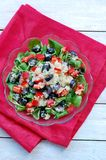 Fresh healthy vegan salad with quinoa, corn salad, black olives, red pepper and olive oil in glass bowl on red cloth on white wood Royalty Free Stock Photography