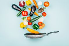 Fresh healthy vegetables falling in a pan stock images