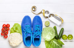 Fresh healthy vegetables, sneakers on white wood background. Stock Image
