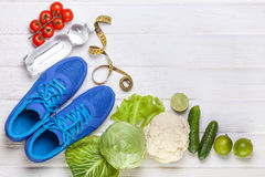Fresh healthy vegetables, sneakers on white wood background. Royalty Free Stock Photography