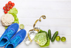 Fresh healthy vegetables, sneakers on white wood background. Stock Photography