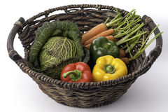 Fresh healthy vegetables in a traditional woven basket. Organically grown savoy cabbage; carrots and peppers in a traditional woven basket displayed aganst a Stock Photography