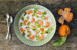 Fresh and healthy vegetarian breakfast set: a bawl of yogurt wit. H fresh kiwi and mandarins over a rough wooden desk. Top view Stock Photography
