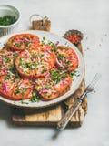 Fresh heirloom tomato, parsley and onion salad on wooden board. Fresh heirloom tomato, parsley and onion salad in white plate on wooden board over light grey stock images