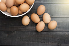 Fresh hen egg in white bowl and 6 hen egg out side on Black colo Stock Photo