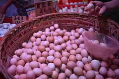 Fresh hen eggs heaped up inside the wicker basket. Fresh hen eggs heaped up inside the  wicker basket. Translation: `hen eggs 8 yuan/half a kilo Stock Photo