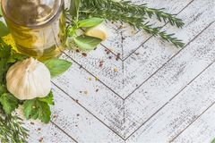 Fresh herb and garlic frame. Olive oil, fresh rosemary, Italian parsley, basil and garlic on white tray sprinkled with red pepper flakes. Framed for text stock image