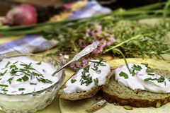 Fresh herb quark. A glass bowl with fresh herb cheese and two slices of bread. In the background more herbs and flowers Royalty Free Stock Photography